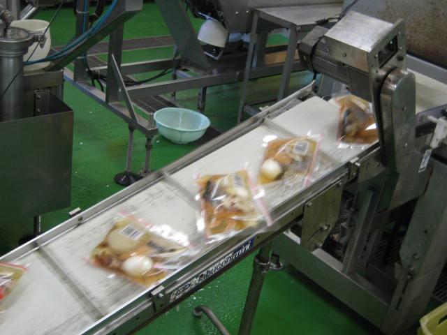 レトルトができるまで 4. 密封されたレトルトパウチはベルトコンベアで次々と送られます。
